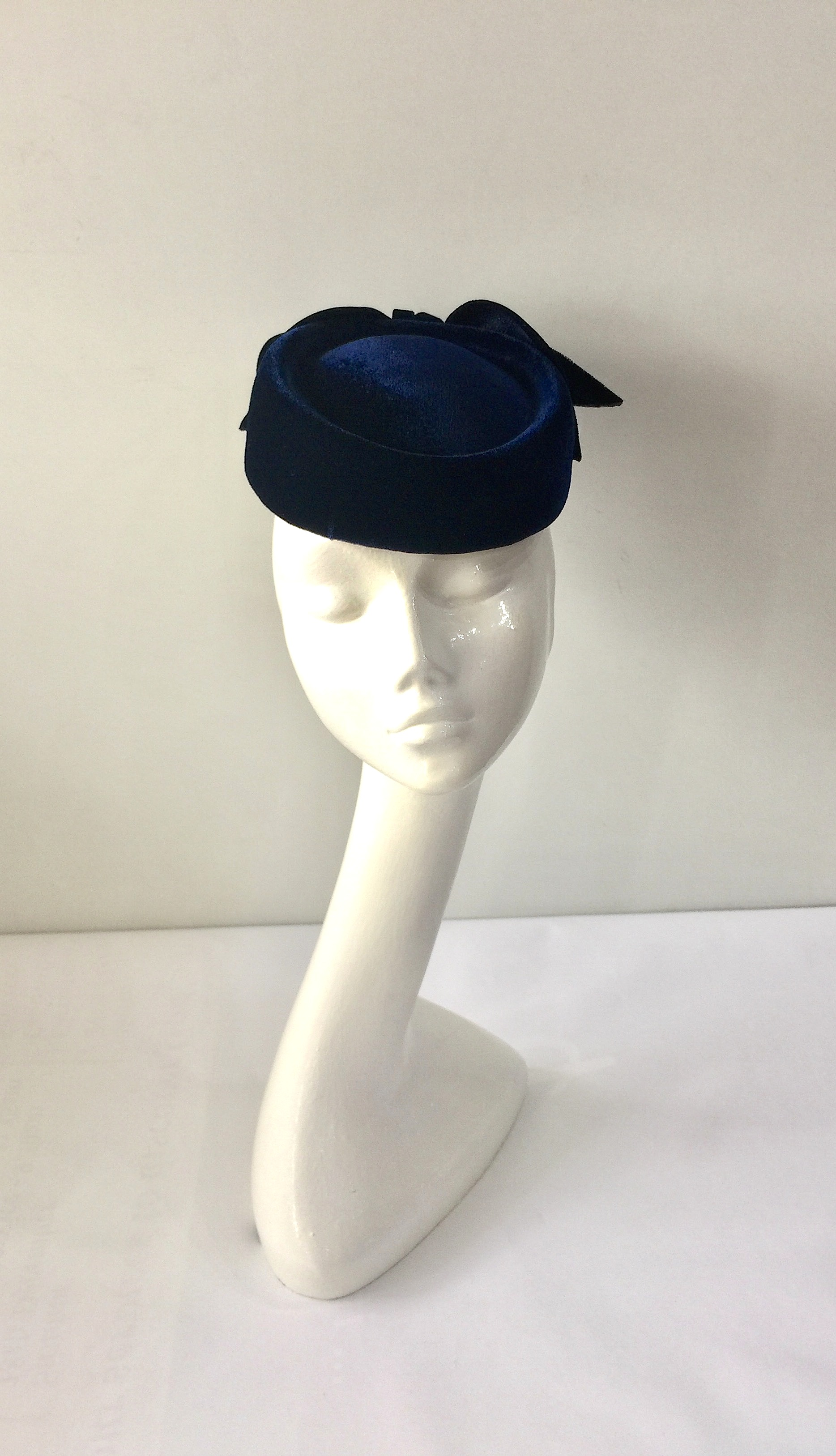 9df15924a8a23 A velvet pillbox hat in navy blue with velvet bow trimming. Hat elastic for  a secure fit.